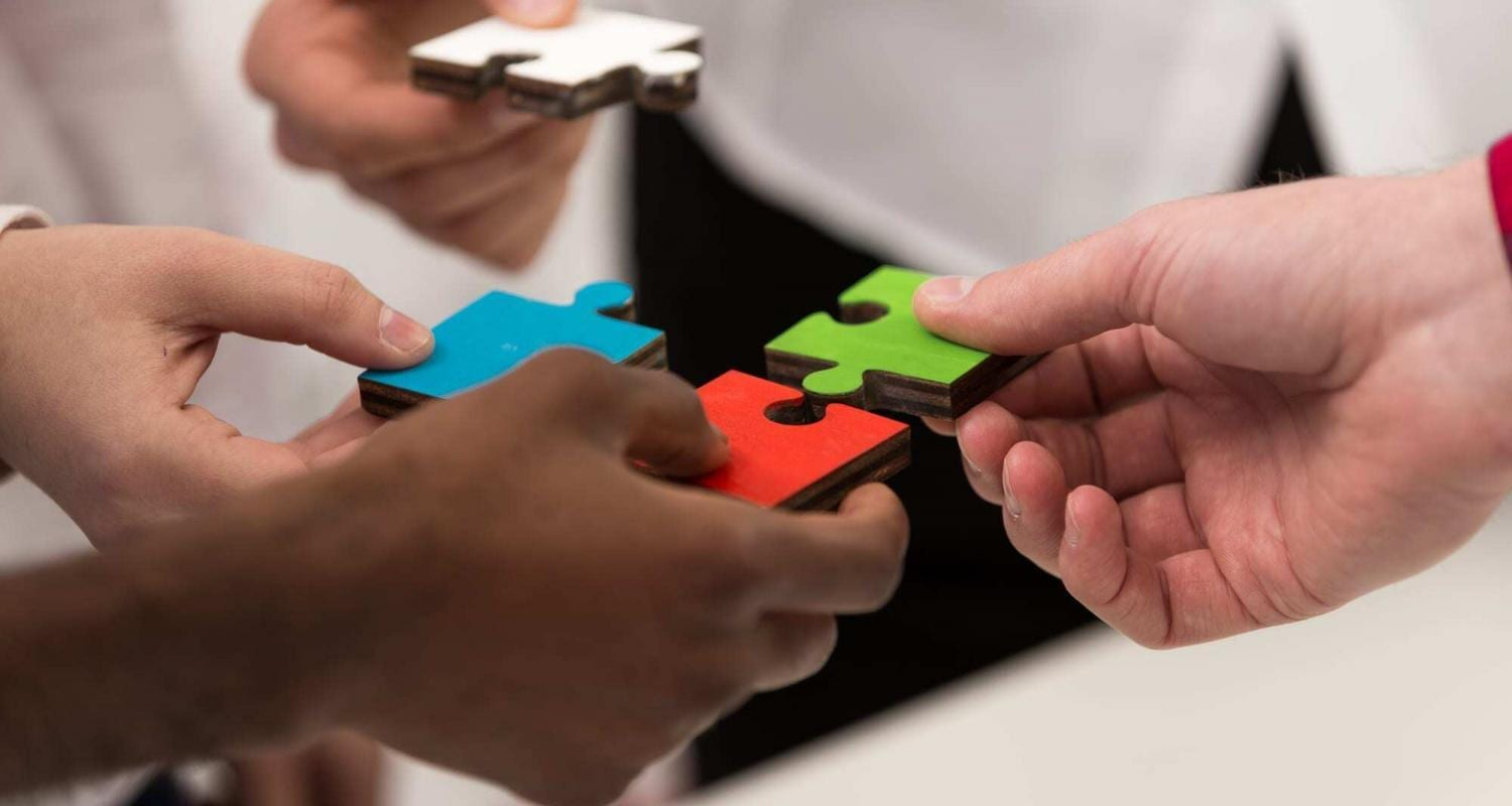 business people group assembling jigsaw puzzle and represent team support